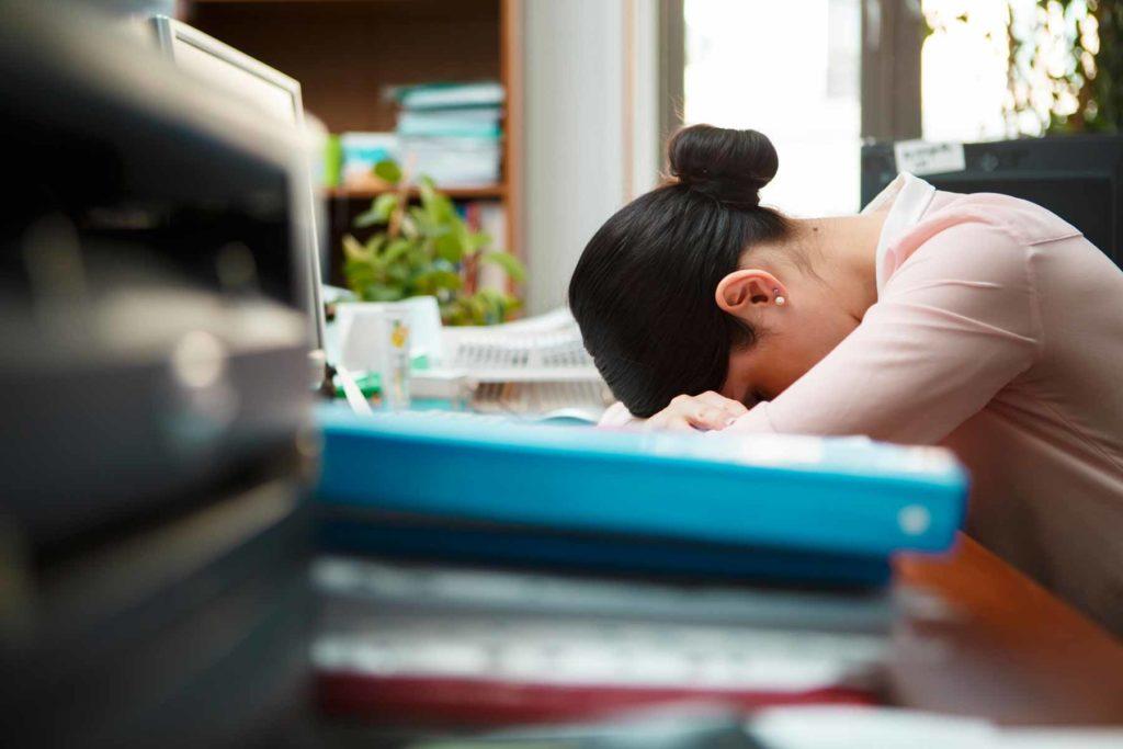 woman sleeping at work due to sleep loss