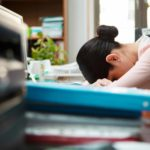 woman sleeping at work due to sleep loss